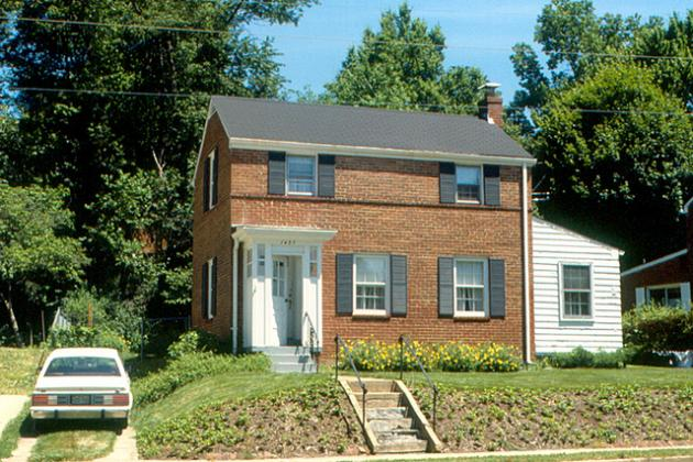 short steep slope in front of a two story brick house