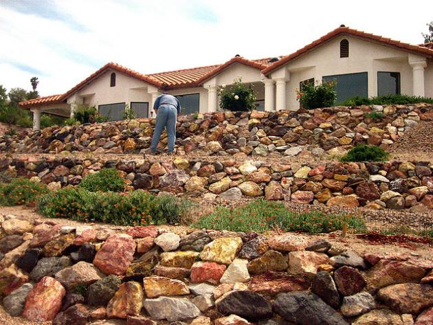 terraced rock retaining walls below a Mediterranean style home