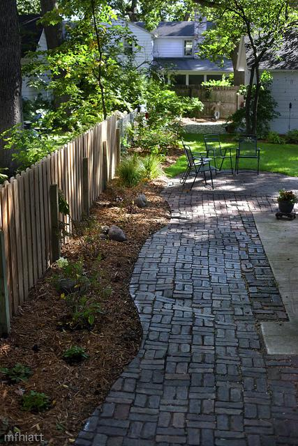 A backyard with a mulched flower bed, paved patio, and fence
