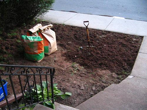 Mixing manure into clay soil in flower bed